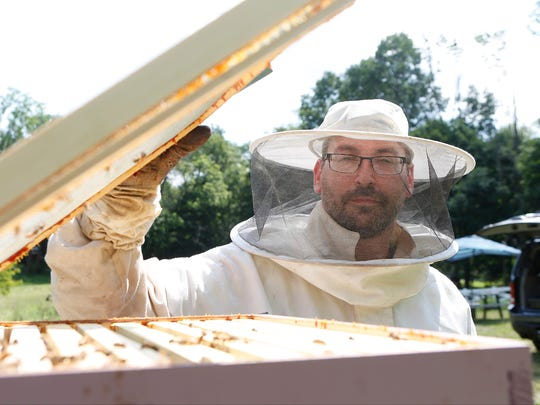 Beekeeper Zev Oster, 39, of Monsey, opens the top to