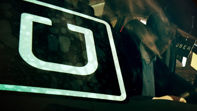 A man checks a vehicle at the first of Uber's 'Work On Demand' recruitment events on March 10, 2016.