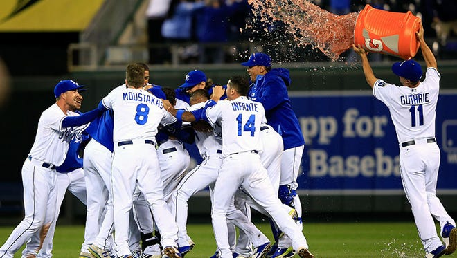 The Royals celebrate as they swarm Lorenzo Cain, who hit the game-winning single to knock in Terrance Gore as they defeat the White Sox, 4-3, Monday in Kansas City, Mo.