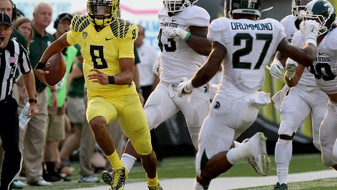 Michigan State defenders try to chase down Oregon QB Marcus Mariota during MSU's loss on Sept. 6 in Eugene, Ore.