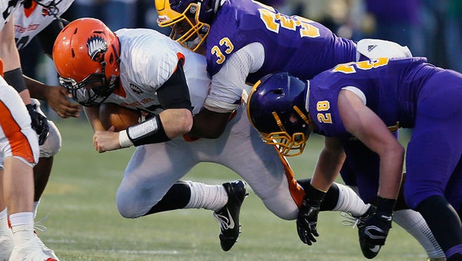 Birmingham Brother Rice quarterback Alex Malzone is sacked by Warren De La Salle's Eric Rogers, center, and Austin Potter, bottom, in the second quarter of Rice's 28-21 win Friday at Wayne State.