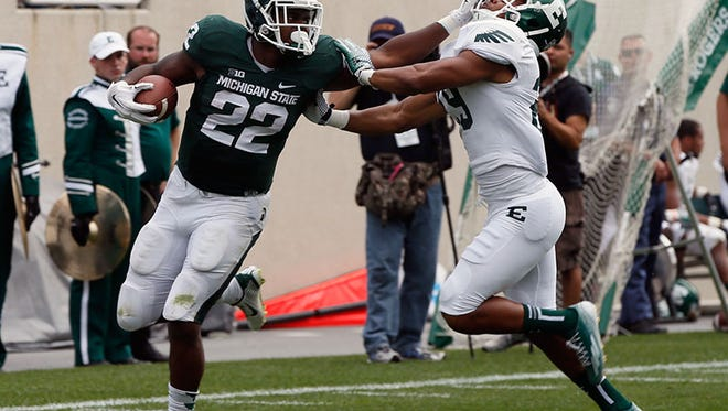 Michigan State running back Delton Williams stiff arms Eastern Michigan's Jalen Williams to complete his run to the end zone on an 80-yard touchdown run in the fourth quarter of MSU's 73-14 win Saturday in East Lansing.