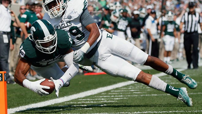 Michigan State's AJ Troup leaps into the end zone past Eastern Michigan's Jason Beck for a touchdown in the second quarter Saturday in East Lansing.