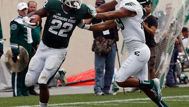 Michigan State running back Delton Williams stiff arms Eastern Michigan's Jalen Williams to complete his run to the end zone on an 80-yard touchdown run in the fourth quarter of MSU's 73-14 win over EMU in East Lansing on Saturday.