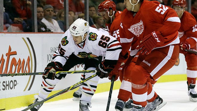 Blackhawks center Andrew Shaw (65) controls the puck while defended by Red Wings defenseman Jonathan Ericsson (52), of Sweden, during the first period of the Wings' 3-2 win Thursday in Detroit.