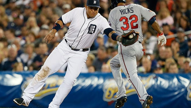 Tigers first baseman Miguel Cabrera is pulled off the bag on a throw to try to get Twins centerfielder Aaron Hicks during Friday's game at Comerica Park.