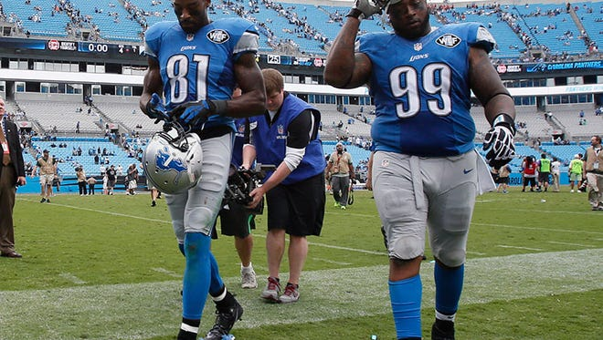 Lions Calvin Johnson and C.J. Mosley walk off the field after their 24-7 loss to the Panthers in Charlotte, N.C., on Sept. 14.