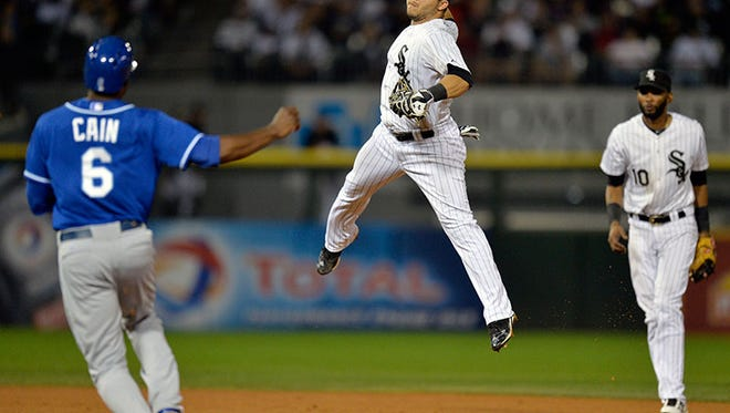 White Sox second baseman Carlos Sanchez forces out the Royals' Lorenzo Cain and leaps into air as he throws to first base to complete a double play during the eighth inning Saturday in Chicago.