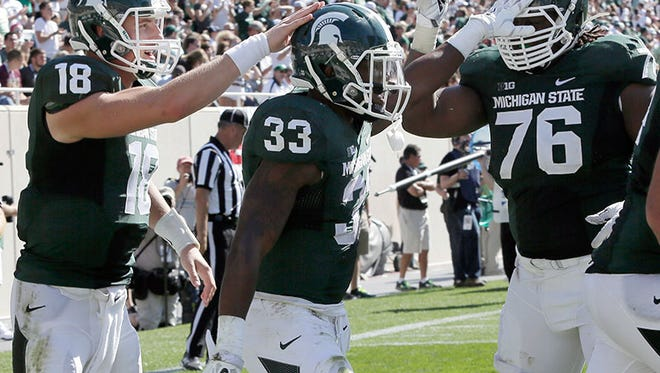 Michigan State's Connor Cook, Jeremy Langford and offensive lineman Donovan Clark celebrate a touchdown Saturday in East Lansing.