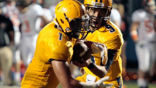 Dearborn Fordson's Muhammed Zahr hands the ball to Jamil Sabbagh during the win over Dearborn on Friday.