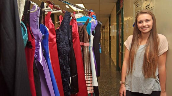 Grace Chesterman poses with some of the formal dresses she's collected in a drive to help students in need. (Carucha Meuse)