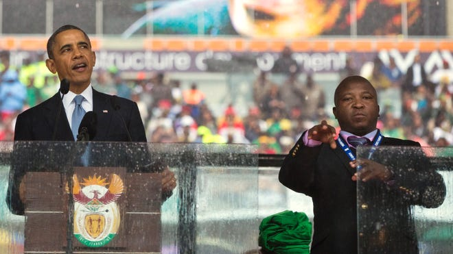 Thamsanqa Jantjie, right, interprets in sign language for President Barack Obama during his remarks at a memorial service at FNB Stadium in honor of Nelson Mandela in Soweto, near Johannesburg.