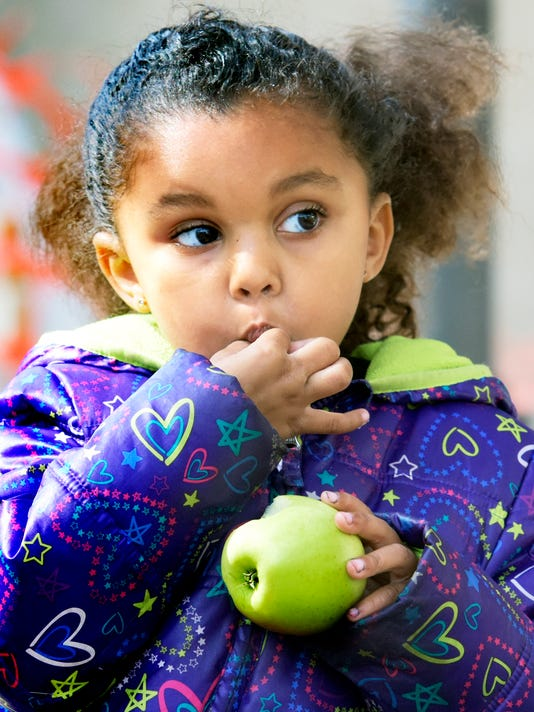 """Deanna Miles, 4, of York City, eats an apple in Continental Square during pop-up Apple Handout Station Tuesday, Oct. 20, 2015. She was running errands with her mother. As part of its month-long """"Starts With Apples"""" campaign, Family First Health staff and volunteers handed out the fruit and health information to the lunchtime crowd passing through the square. The annual event is held in October to coincide with National Healthy Literacy Month and National Apple Month. Brown's Orchards donated 250 apples for the event. Bill Kalina - bkalina@yorkdispatch.com"""