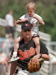 -  -Ryan Ripken playfully taps away on the head of his father, Baltimore Orioles third baseman Cal Ripken while riding on his shoulders on the field prior to a spring training game against the New York Mets in Fort Lauderdale, Fla. Thursday, March 11, 1999.(AP Photo/Roberto Borea)