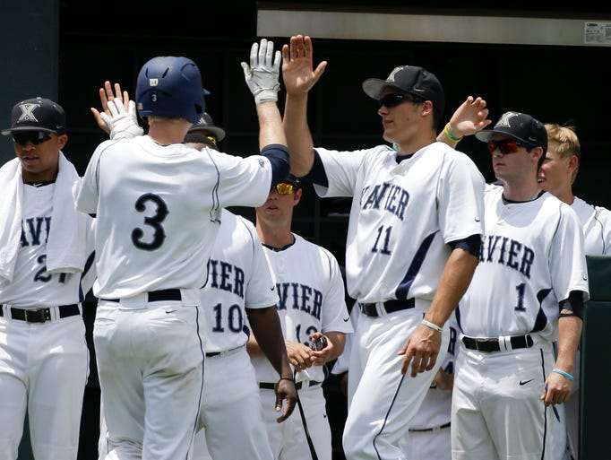 Xavier's Daniel Rizzie (3) is congratulated by Joe Forney (11) after Rizzie scored on a RBI double by Patrick Jones during the first inning against Clemson in an NCAA college baseball regional tournament game Saturday, May 31, 2014, in Nashville, Tenn. (AP Photo/Mark Humphrey)