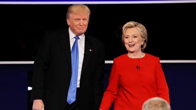 Republican presidential nominee Donald Trump and Democratic presidential nominee Hillary Clinton walk across the stage after the presidential debate at Hofstra University in Hempstead, N.Y., Monday, Sept. 26, 2016.