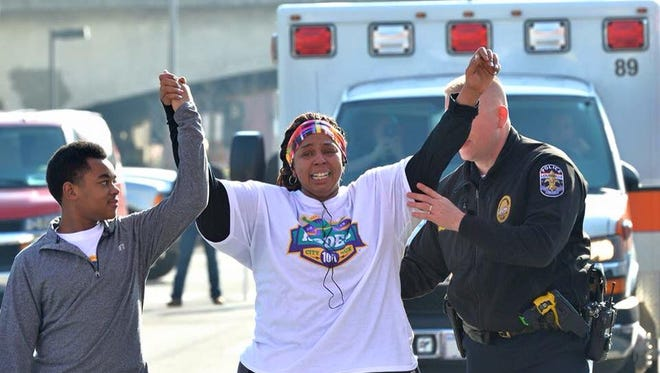 Asia Ford throws up her arms when crossing the finish line, thanks to help from her son and Lt. Aubrey Gregory.