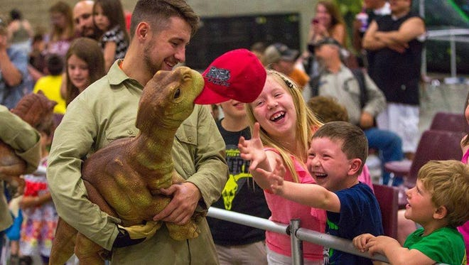 A dinosaur takes the hat off of a child attendee of a Jurassic Quest event.
