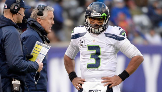Seattle Seahawks head coach Pete Carroll (left) talks with quarterback Russell Wilson (3) during the game against the New York Giants at MetLife Stadium.