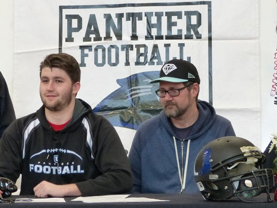 U-Prep's Bradley Patenaude, center, signed Wednesday to play football for Western Oregon University in front of mother Mary Dopp (from left), stepfather Karsten Lapp, father Sean Patenaude and stepmother Jewel Martin.