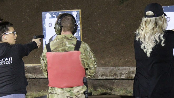 Jessica Stokes (left) gets a few shooting tips from instructor Phil Sage while Jamee Garner (right) sights her target Tuesday night during the Citizens Police Academy at the Abilene Police Department's training facility.