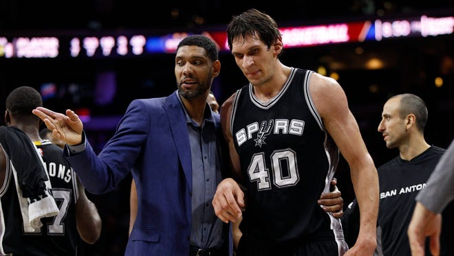 Tim Duncan, left, talks with Boban Marjanovic during a game last season.