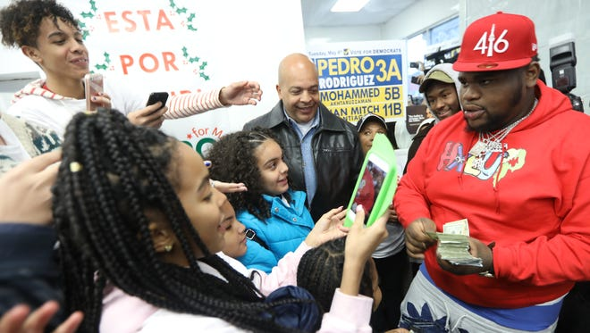 Fans take pictures of entertainer Fatboy SSE as he gives out $20 bills at campaign headquarters for Pedro Rodriguez in Paterson. Sunday April 15, 2018