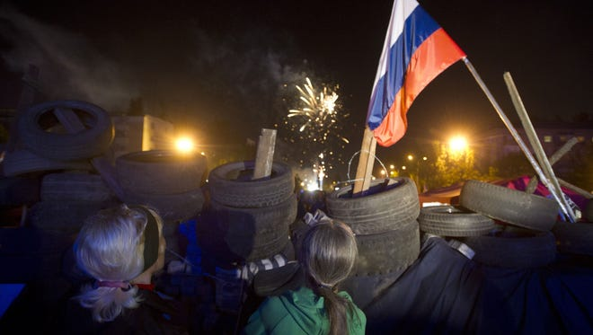 Pro-Russia supporters look at fireworks as they gather outside the regional state building in the eastern Ukrainian city of Donetsk on May 12.