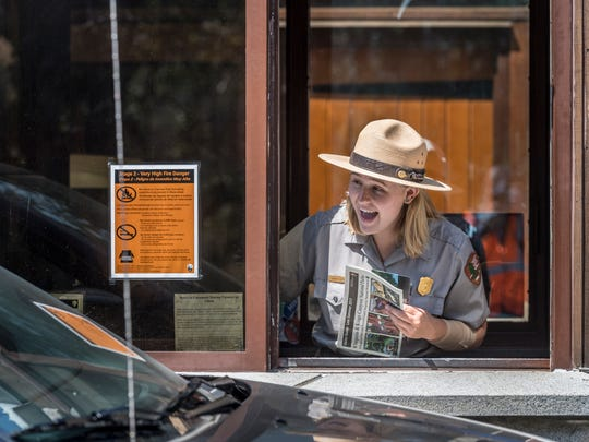 Hannah Cantrell greets visitors to Sequoia National Park on Friday, August 25, 2017. Many visitors were surprised by the free entrance in celebration of the 101st birthday of the National Park Service.
