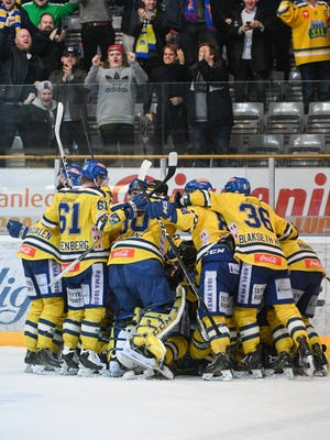 Storhamar players celebrate after Joakim Jensen scored to end a record-breaking hockey match in the Norwegian League playoffs in Hamar, Norway, on March 13, 2017.