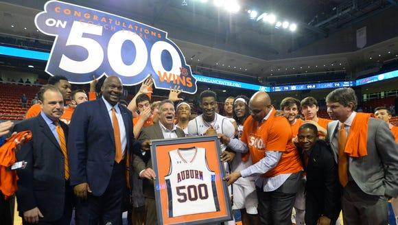 Auburn coach Bruce Pearl, holding plaque, celebrates