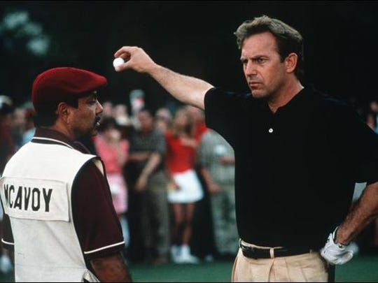 """Kevin Costner takes a drop for another shot after reaching the green in the pivotal scene of """"Tin Cup."""""""
