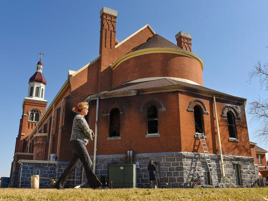 Deb Streese, Sauk Center, walked around the Church of St. Mary  Saturday, March 12, to see the damaged caused by fire Friday nigh to the church in Melrose.