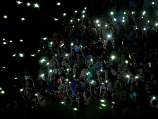 The crowd uses their cell phones to light up the evening
