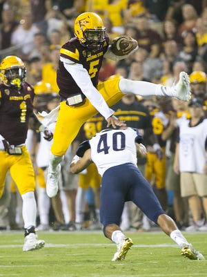 ASU quarterback Manny Wilkins jumps over NAU safety Keith Graham during the second quarter of the ASU football season opener at Sun Devil Stadium in Tempe on Saturday, September 3, 2016.