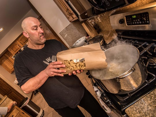 At his home in Ocean Township, Tom Fornicola pours fresh fusilli from Pasta Volo in Asbury Park into a large pot as he prepares an Italian dinner.