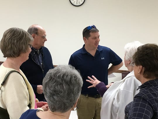 New Ward 1 Alderman Mike Pulley, center, talks with a group of Colson Village condominium residents who say he only cuts the grass at the complex twice per year.