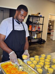 CHOW employee Shunta Burk fills individual containers with homemade corn casserole.
