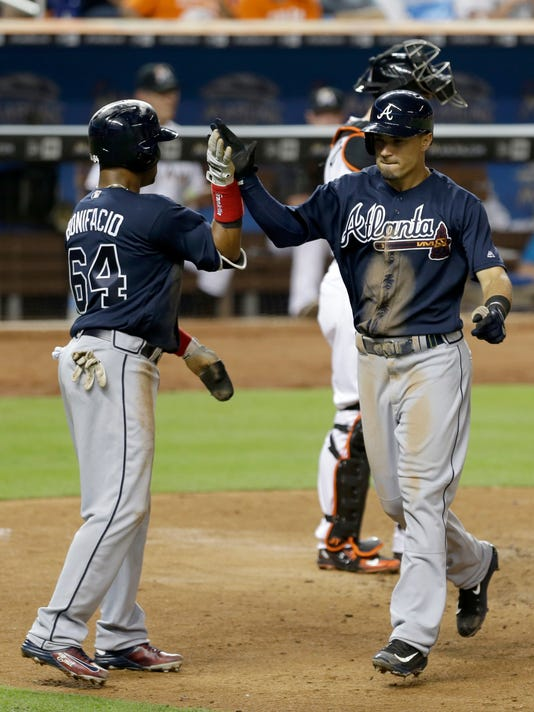 Atlanta Braves' Jace Peterson, right, is congratulated by teammate Emilio Bonifacio (64) after hitting a two-run home run against the Miami Marlins in the eighth inning of a baseball game, Tuesday, June 21, 2016, in Miami. Bonifacio scored on the home run. The Braves won 3-2 in 10 innings. (AP Photo/Alan Diaz)