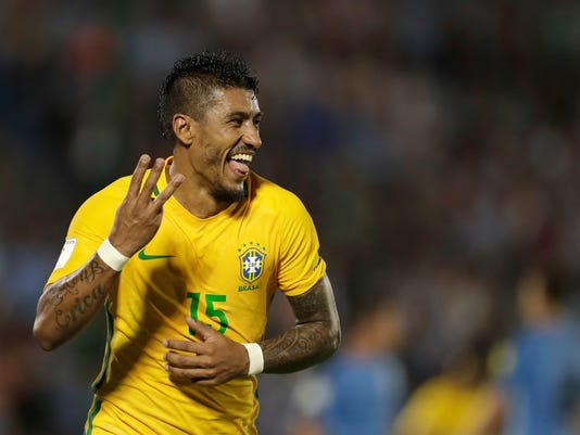 FILE- In this Thursday, March. 23, 2017 file photo, Brazil's Paulinho celebrates his hat trick during a 2018 World Cup qualifying soccer match against Uruguay in Montevideo, Uruguay. Barcelona says it has reached a deal with Chinese club Guangzhou Evergrande to buy Brazil midfielder Paulinho for 40 million euros ($47 million). (AP Photo/Natacha Pisarenko, File)
