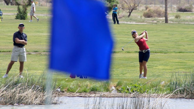Deming High golf coach James Williams watched an approach shot from a Lady Cat player during a past high school tournament. Many of the DHS state champion players have been through junior programs at Rio Mimbres Golf Course in Deming.