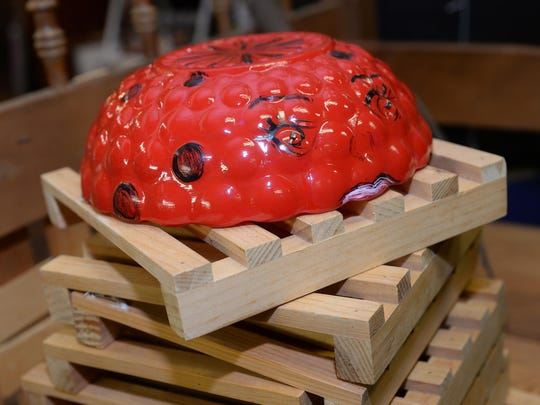 Lisa Dagostino, owner of Wise Buys thrift store, painted a glass bowl to look like a ladybug, creating an accessory that can be used to cover tree stumps or pipes