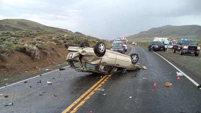 Nevada Highway Patrol officers work to clear the road of a single-car rollover accident Wednesday afternoon along Pyramid Way and Ironwood Road north of Sparks. The accident seriously injured two men and prompted authorities to close the road.
