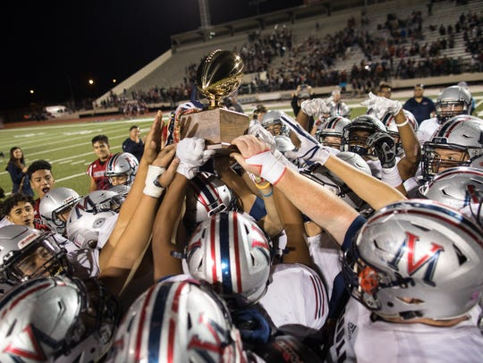 Eagles hold up a trophy after winning the 5A Division