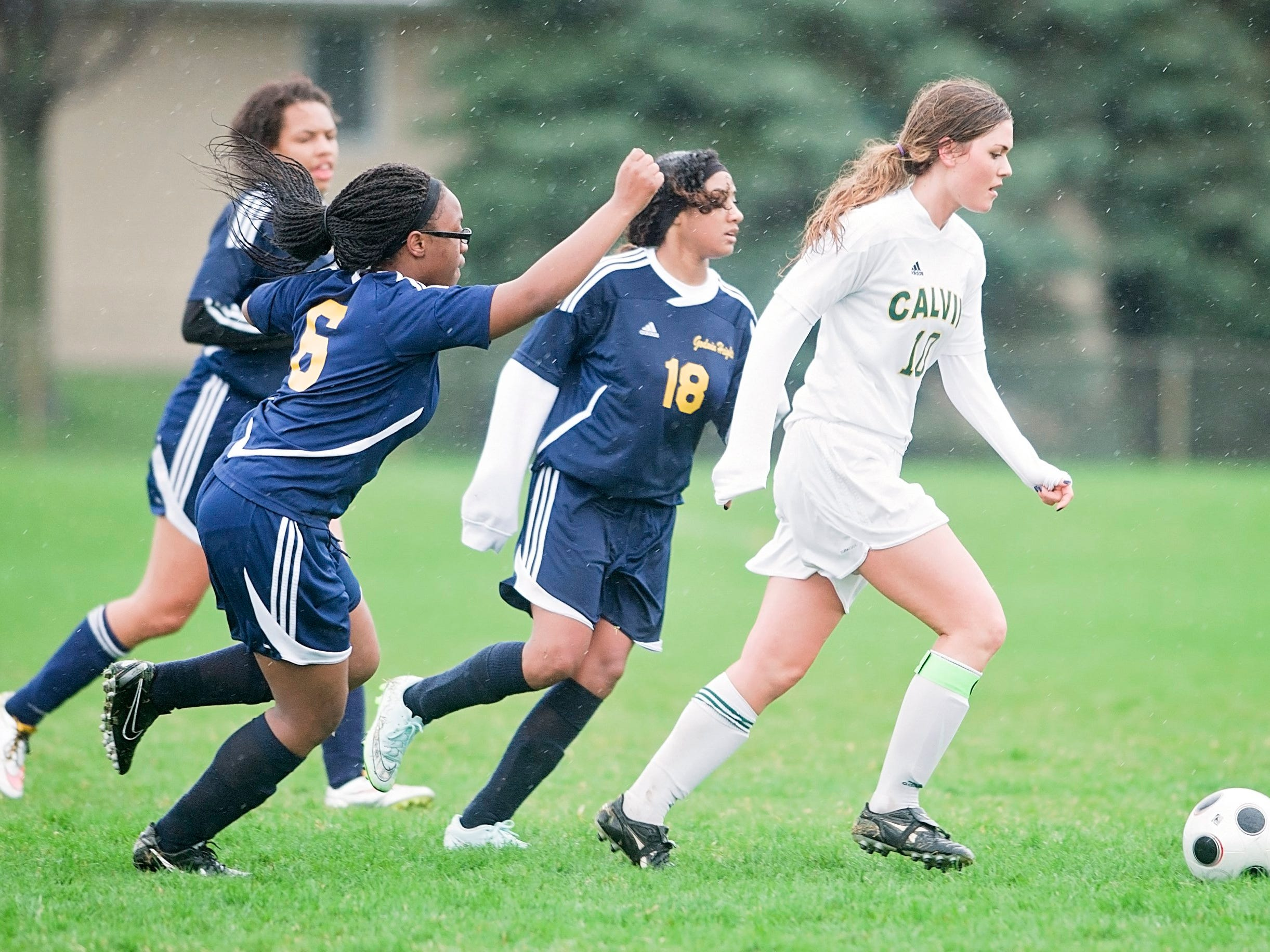 Calvin Christian's Morgan Buursma moves the ball upfield past a trio of Godwin Heights defenders during their game on Monday, April 20, 2015. Calvin Christian defeated Godwin Heights 8-0.(Erik Holladay / Special to the Free Press)