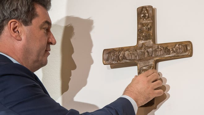 Bavarian state leader Markus Soeder hangs a cross in the entrance area of the Bavarian state chancellery in Munich on April 24, 2018.