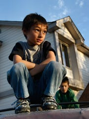 Falcon Henne, 6, perches outside his home Oct. 15,