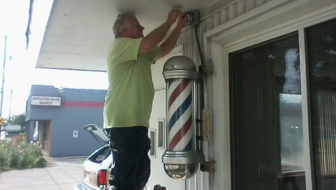 Gary Van Dinter takes down the barber pole in front of Harry Coenen's Barber Shop on Wisconsin Avenue in Appleton.