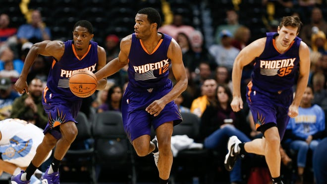 Phoenix Suns forward T.J. Warren (12) dribbles the ball up court ahead of guard Brandon Knight (3) and forward Mirza Teletovic (35) in the second quarter against the Denver Nuggets at the Pepsi Center.