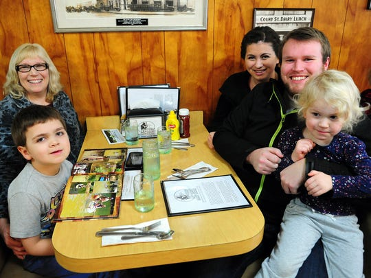 A family lunch consisting of Braylen McEwen, 6, clockwise from left, Suzanne Clarke, Akami McEwen, Aaron Osteen and Alisah Osteen, 3, during Holding Court at Court Street Dairy Lunch on Tuesday, Dec. 23, 2014, in Salem.